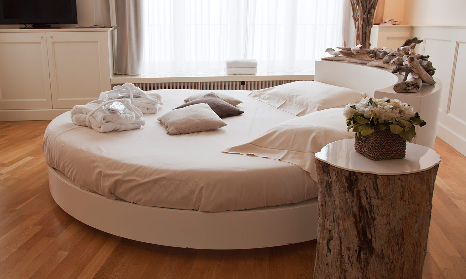 A round bed with pillows on top in a bright and sunny room.