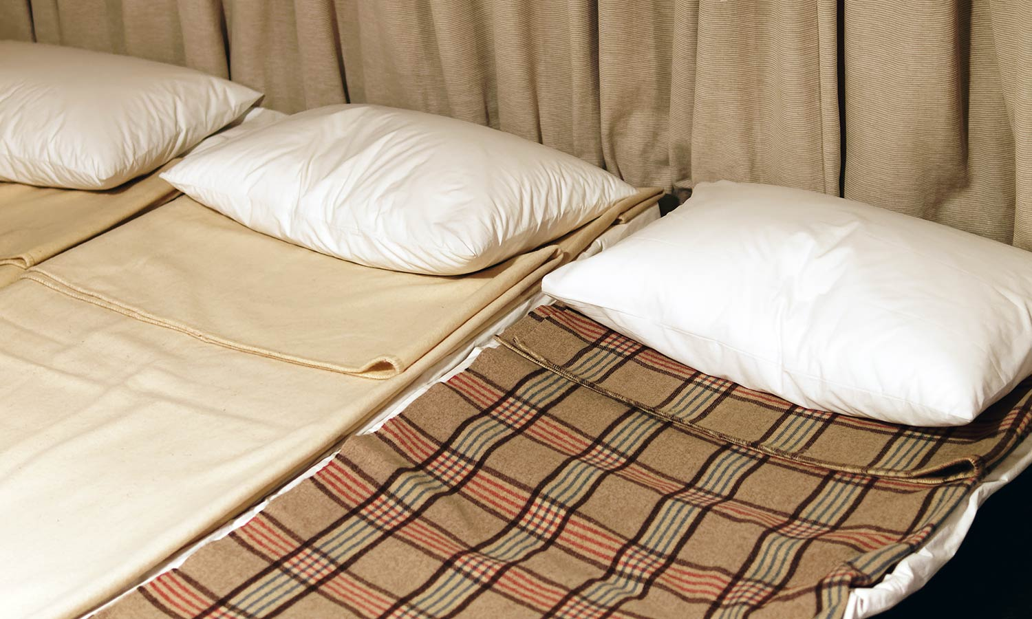 Three small cots next to each other with pillows and thin blankets.