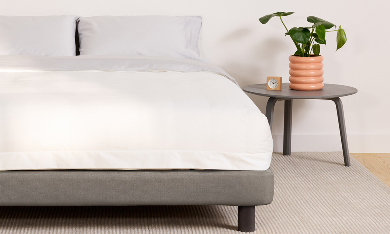 A simple upholstered bed frame with no headboard.