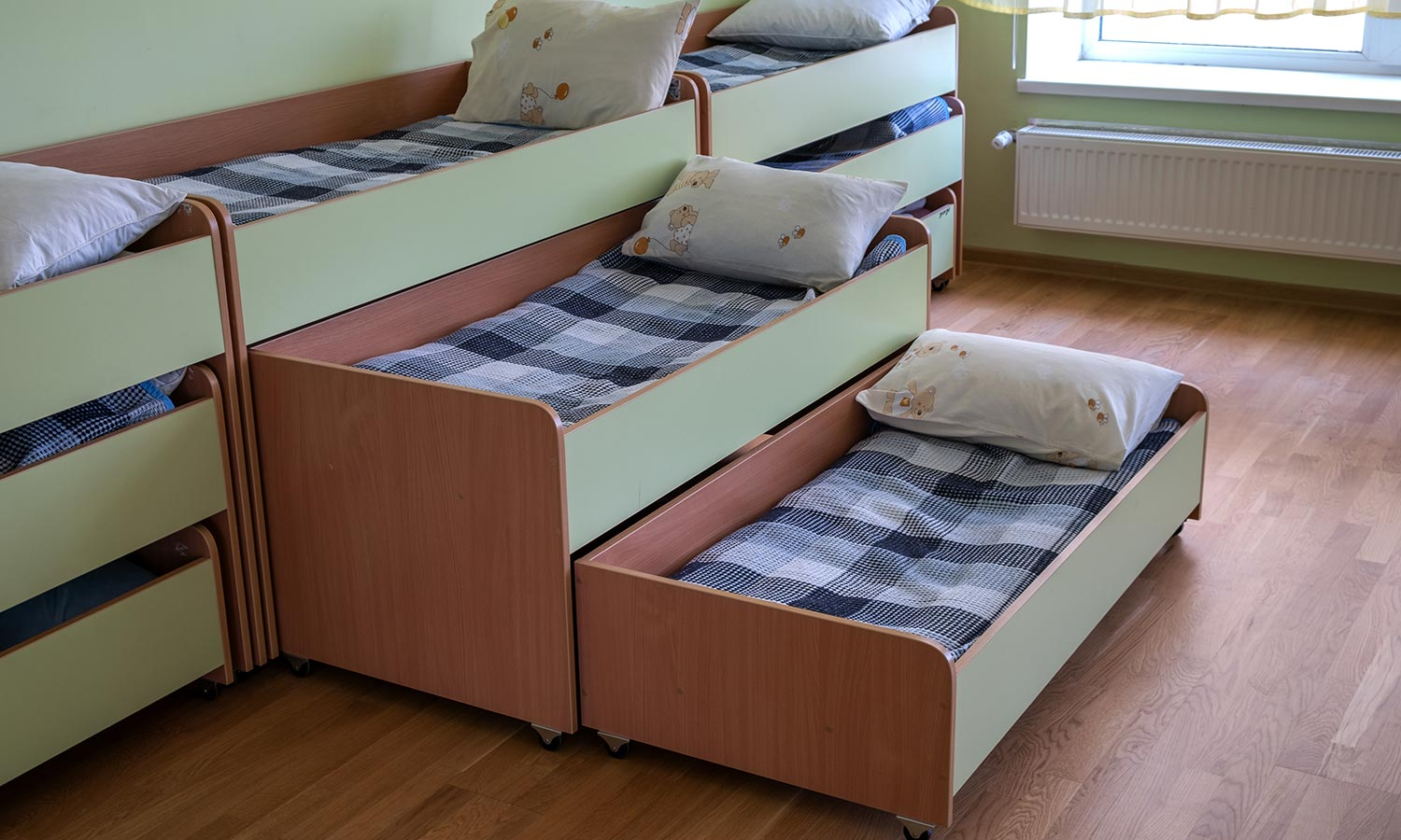 A stacked trundle bed that pulls out to reveal 3 beds in total