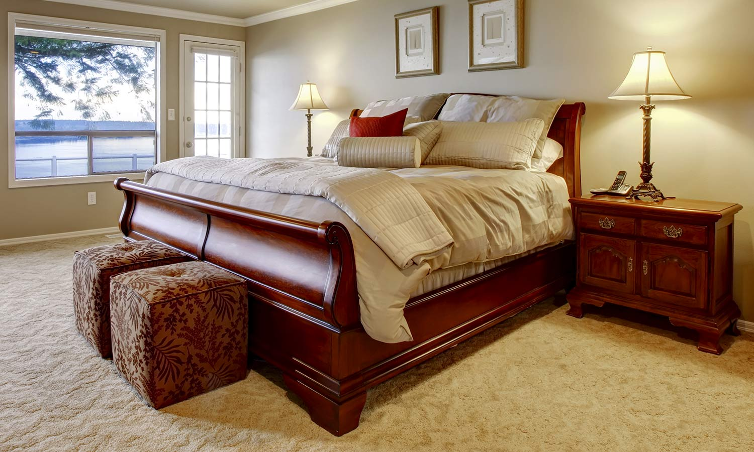 A traditional sleigh-style framed bed, with curving wood at the foot and head.