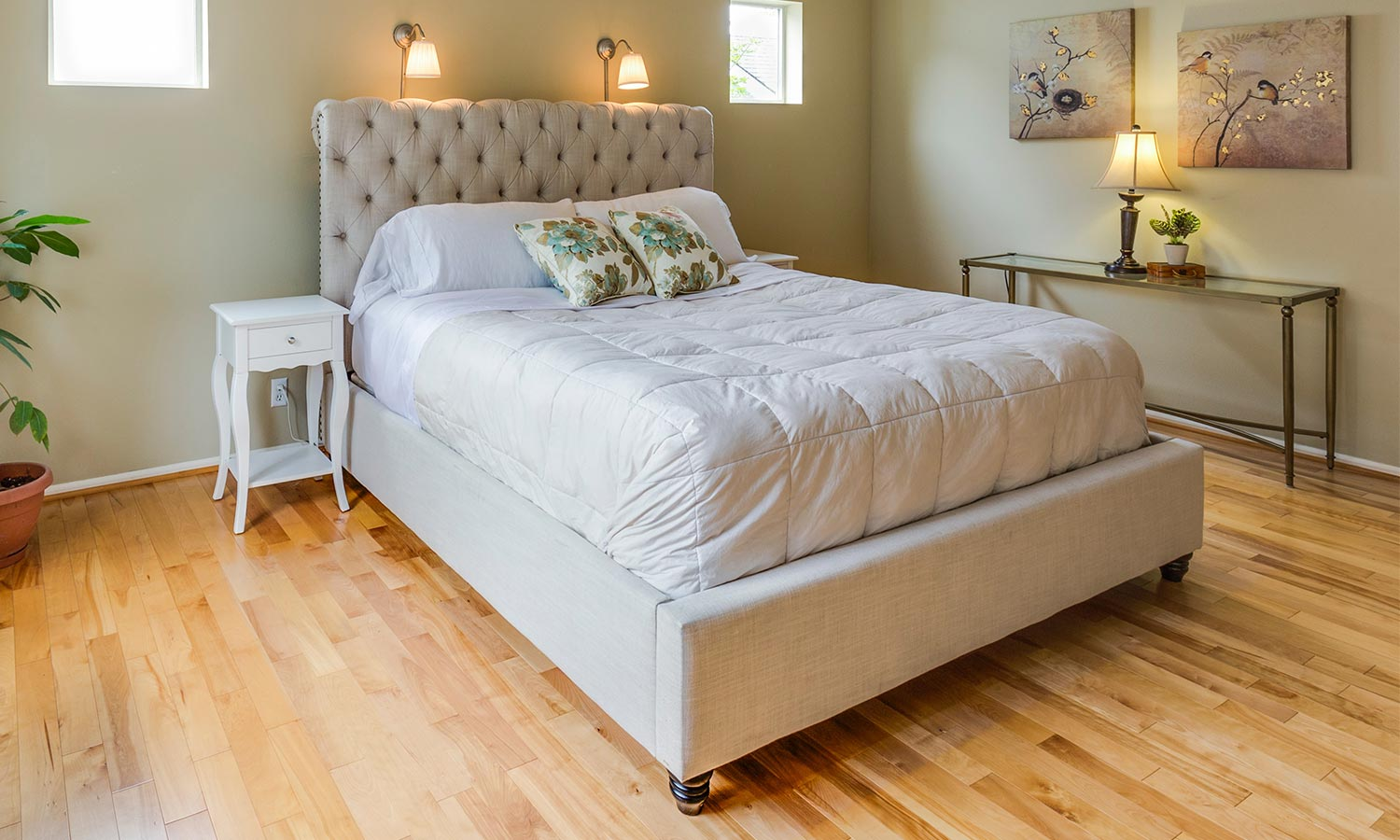 An upholstered bed with a built-in tufted headboard