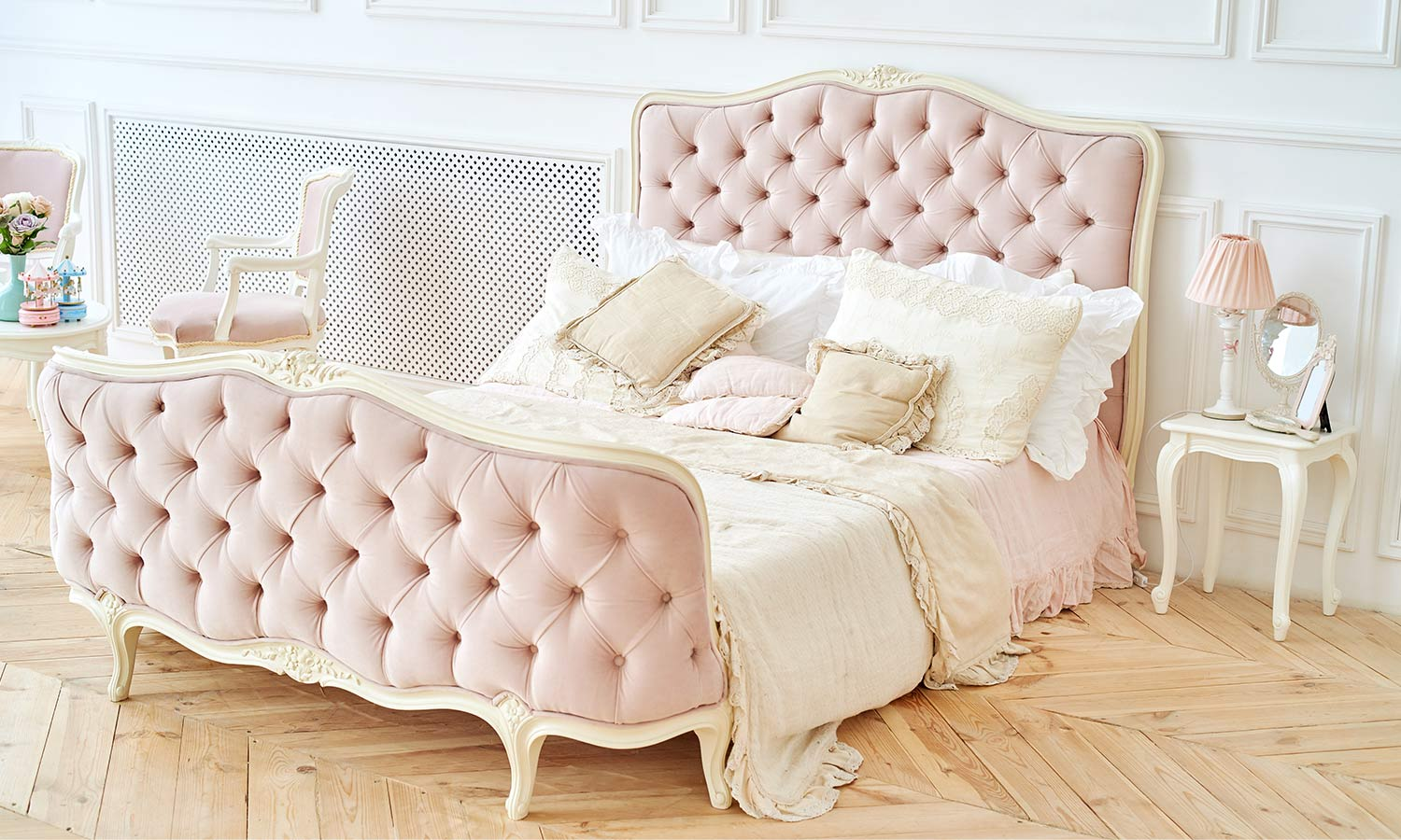 An ornate and bright bed fram tufted on the headboard and footer with thick pink fabric.