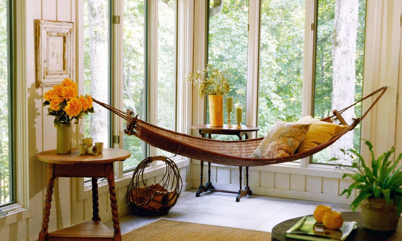 A slim hammock hangs next to a sunny window.
