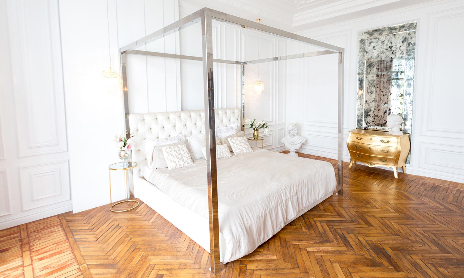 A canopy bed with a shiny metallic frame and no fabric hanging from it.