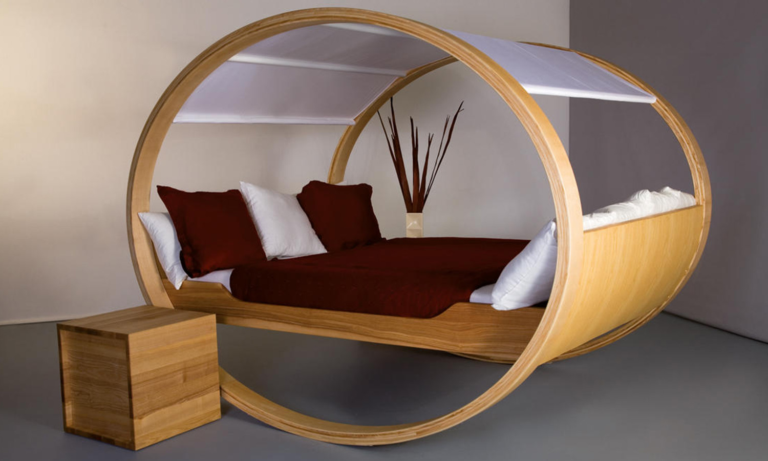 A bed with a vertically-round frame meant for rocking back and forth.