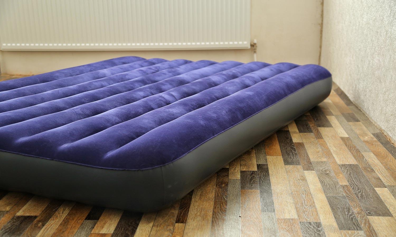 An inflatable air mattress sits on a hardwood floor