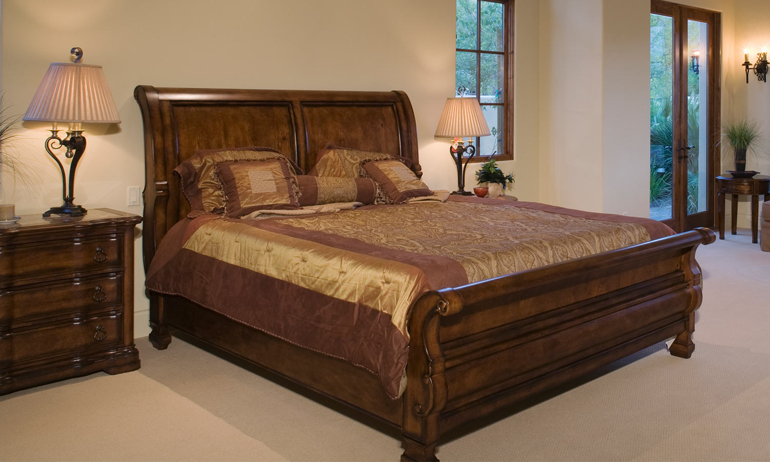 A wooden bedframe witht he headboard and footer curved outwards, resembling a sleigh.