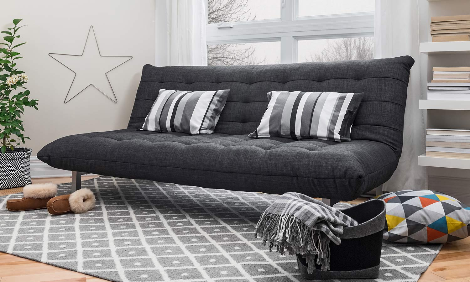 A foldable futon with pillows on top