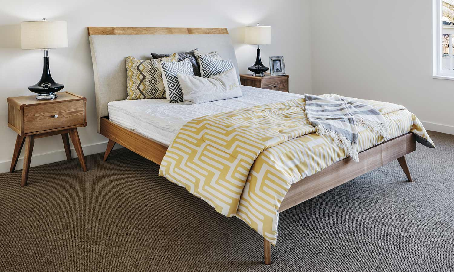 A bed with the legs sitting at an angle with multi-patterned pillows and blankets on top.