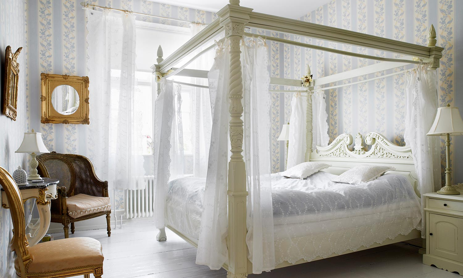 A canopy bed with thin and light fabric hanging from the top corners.
