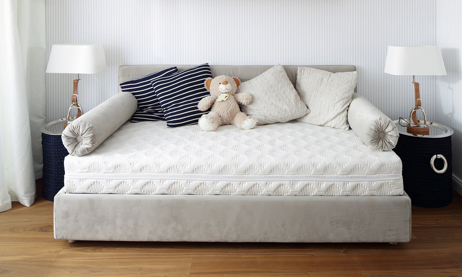 A day bed with pillows and a teddy bear on top