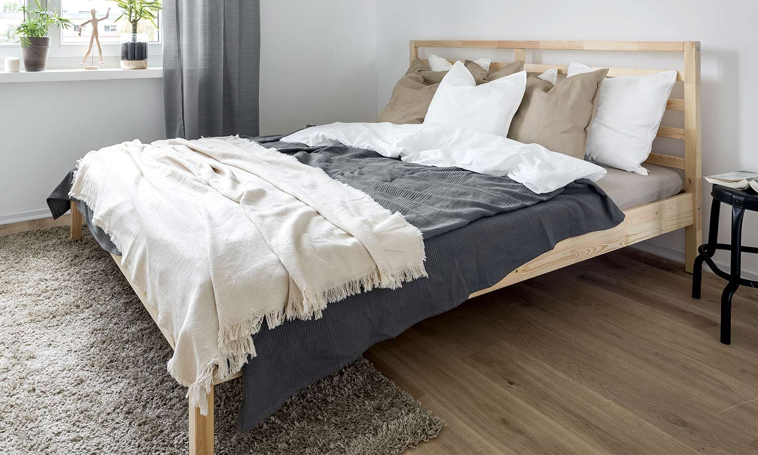 A light-colored wooden frame with a thin and simplistic headboard.