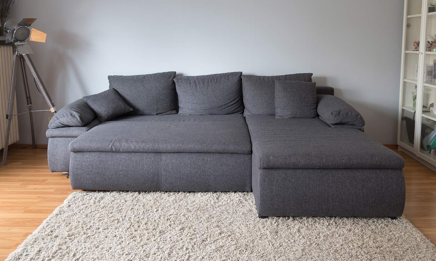 A convertable bed styles as a sofa with big pillows and an attached chaise lounge.
