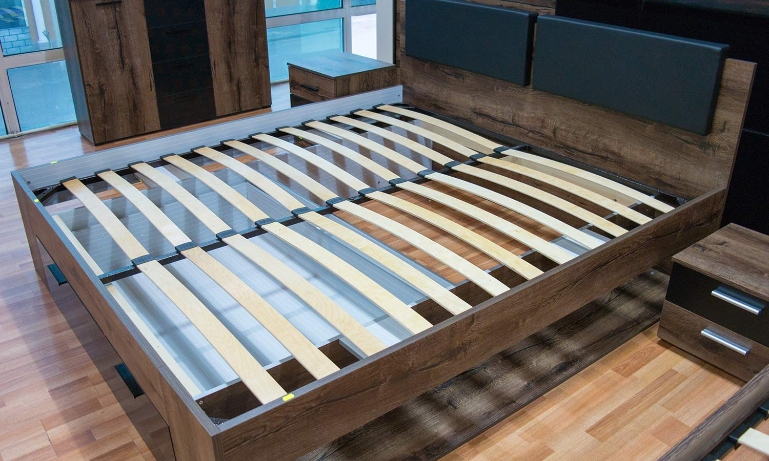 A bed frame where curved wooden slats act as a mattress base.