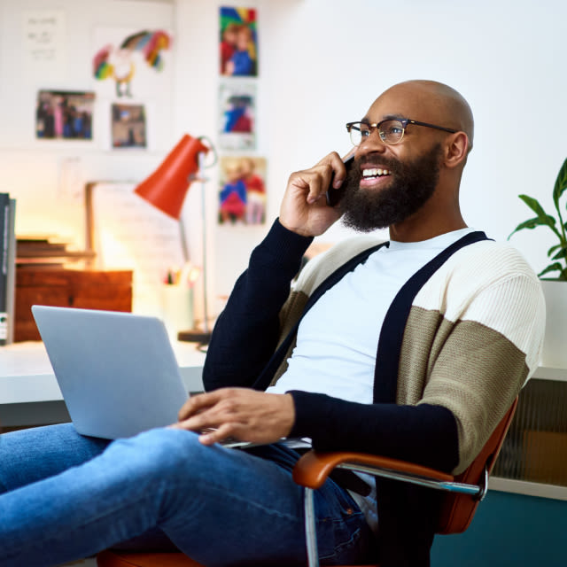 Image of a smiling man on a phone call sitting in a home office.