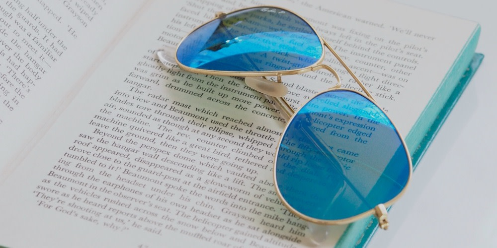 A pair of blue-tinted sunglasses sit on an open book.