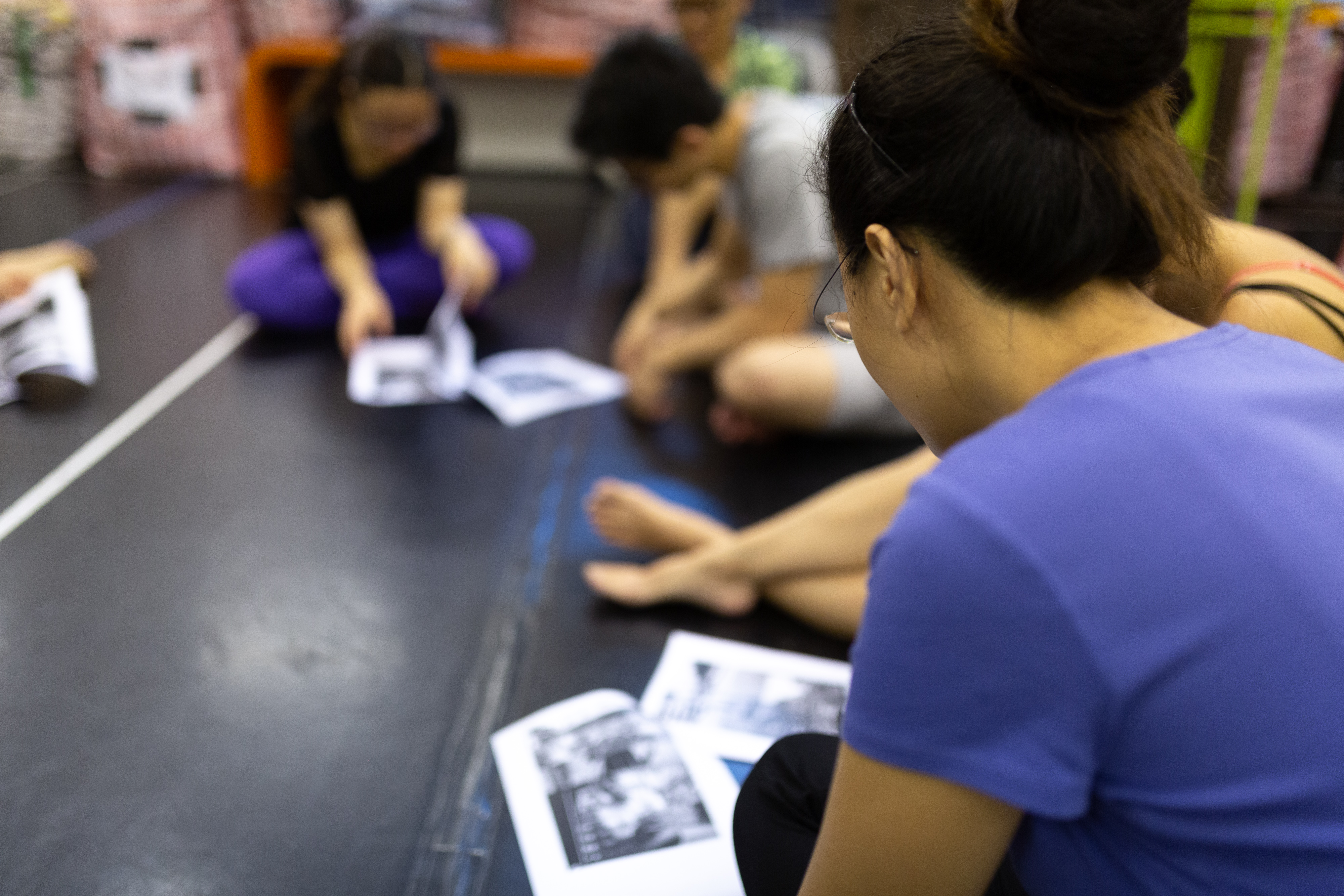 Rooftop Productions • Hong Kong School Drama Courses | Michelle sitting on the floor going over a document with participants in a drama course