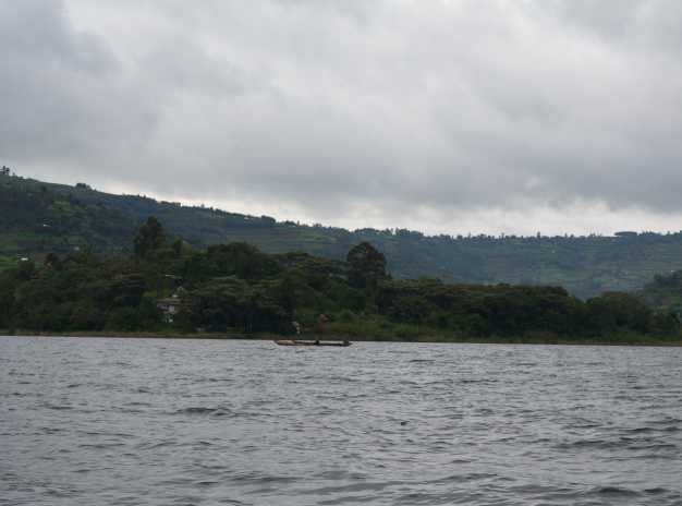 Tourists peacefully boating through the charming lake bunyoni and viewing the Uganda mountains