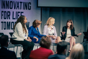 4 women sit in chairs on a stage and one is speaking while the others look toward her.