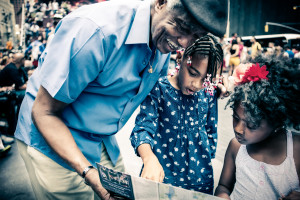 An older man smiles and shows something in a booklet to two younger girls.