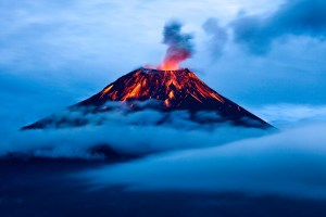 A faraway shot of an active volcano with smoke billowing from the top.