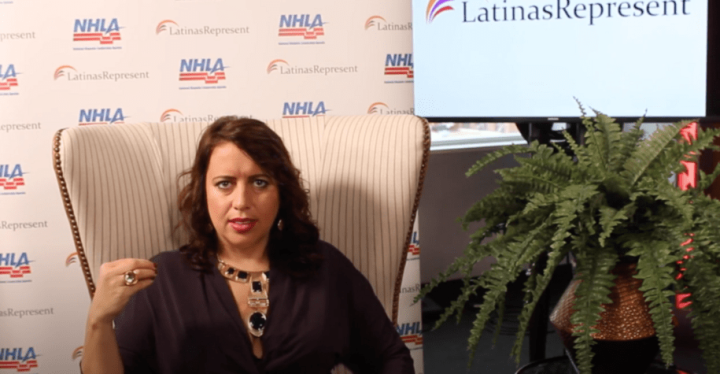 "Natasha Lycia Ora Bannan sits in a chair beside a screen that reads ""Latinas Represent."""