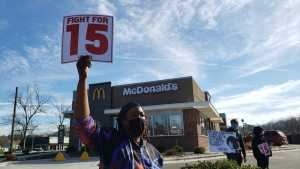 A person wearing a mask stands in front of a McDonald's store holding up a sign that reads