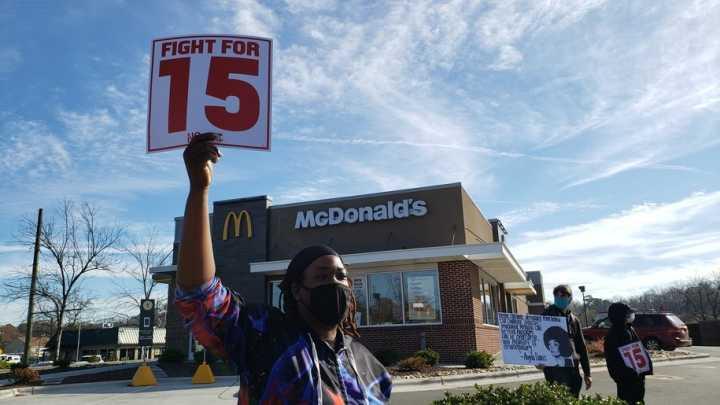 "A person wearing a mask stands in front of a McDonald's store holding up a sign that reads ""Fight for 15"" in red lettering."