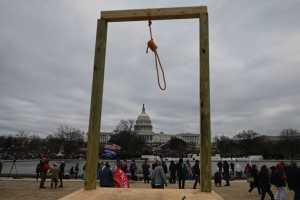 A wooden gallows with a noose stands with the US Capitol building visible in the background.