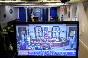 Image of a computer screen in a briefing room, with the numerical breakdown of the impeachment vote on the screen.