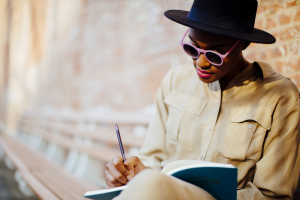 Woman in a hat and sunglasses sits outside in front of a brick wall, writing in a notebook.