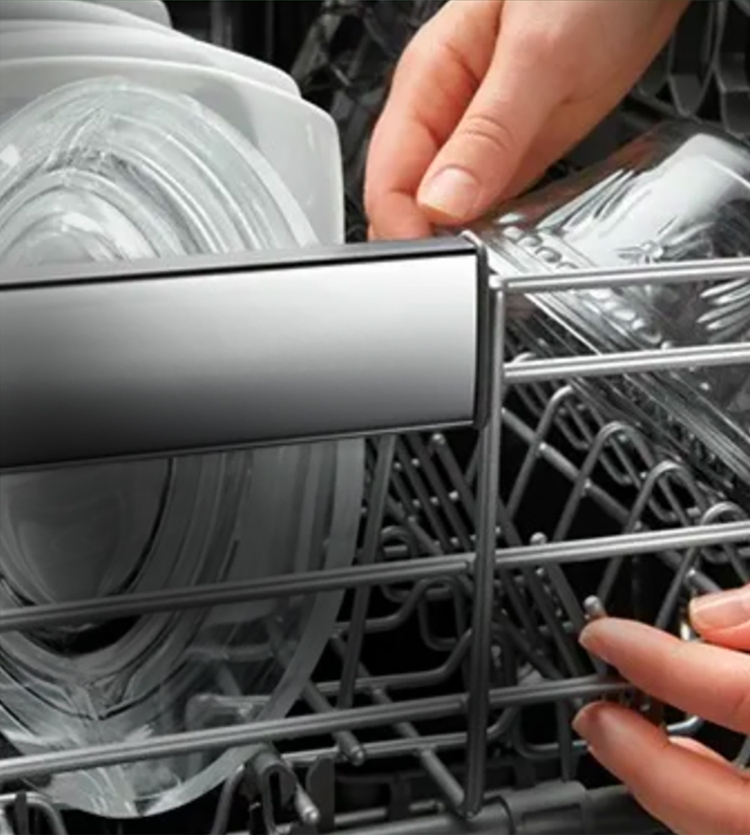 Person offloading clean glass dishware out of dishwasher