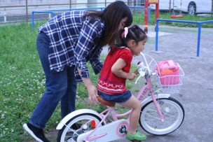 image that parent teaches bicycle to her child