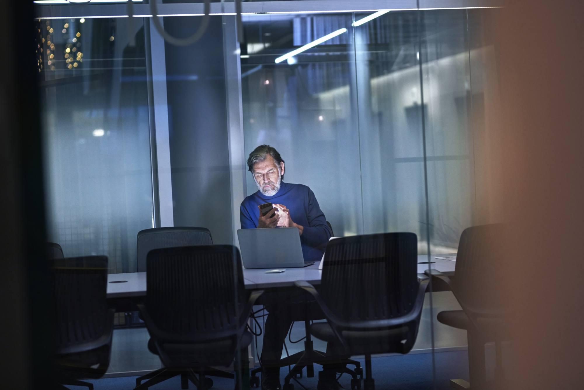 Äldre man i konferensrum med mobil och laptop