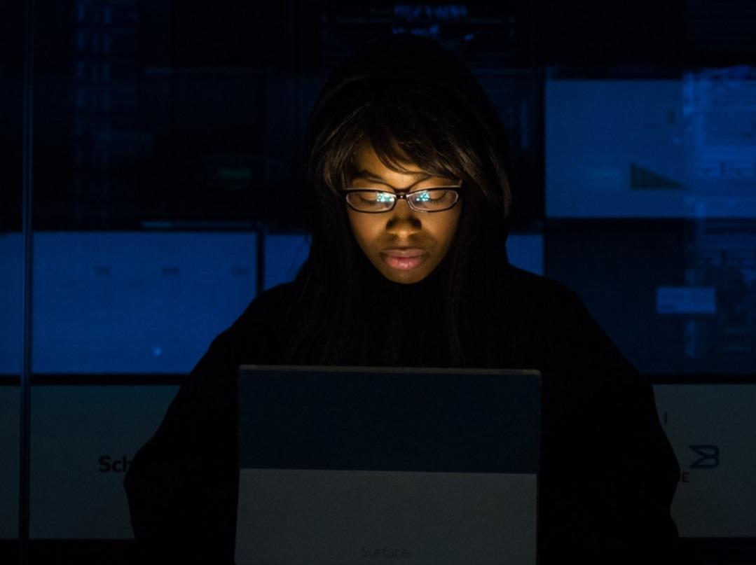Kvinna med laptop i mörkt kontor