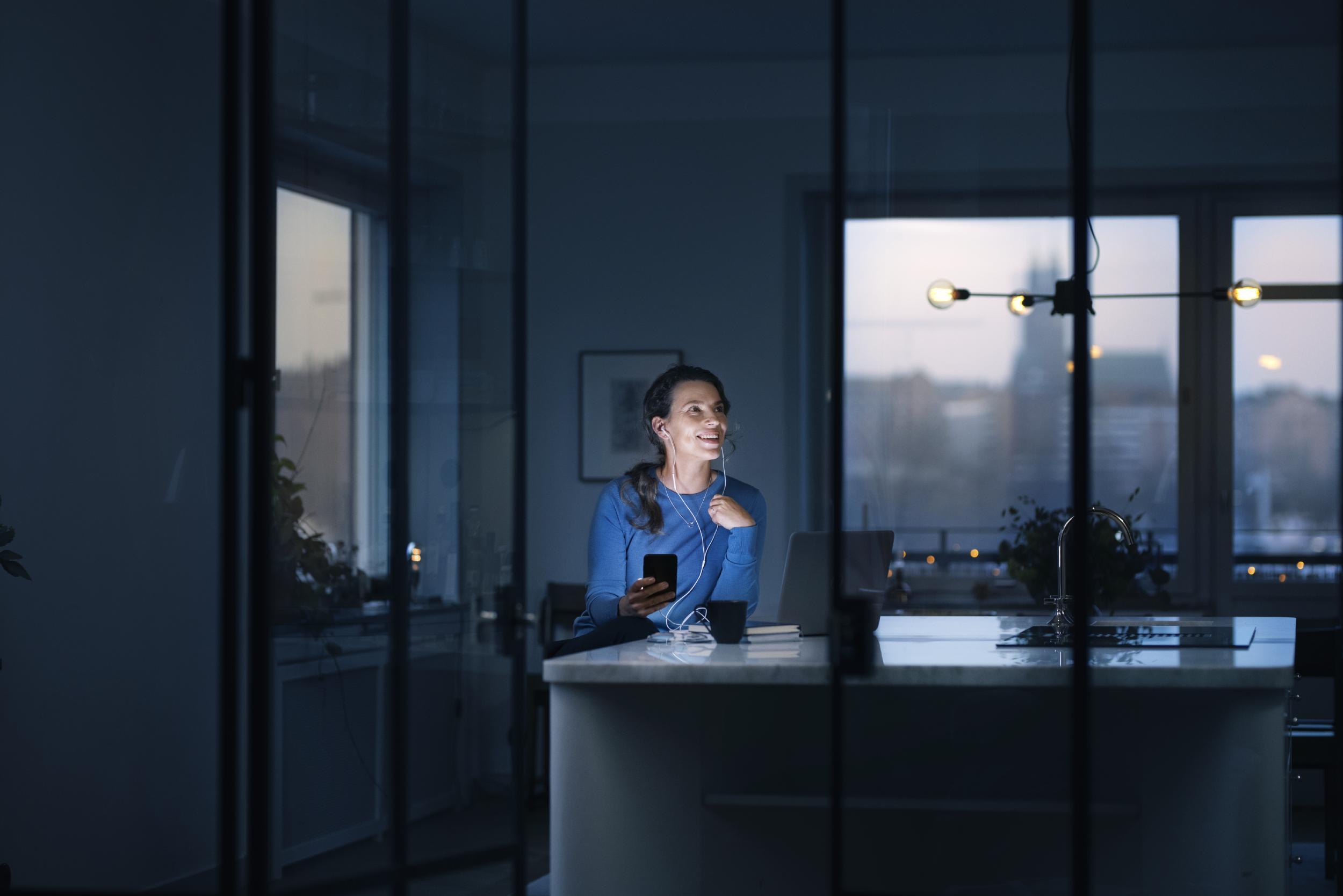 Ung kvinna i blå tröja sitter med mobil vid köksö.