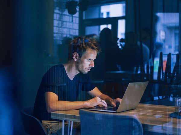Tele2 Företag Ung man med laptop vid bord på restaurang