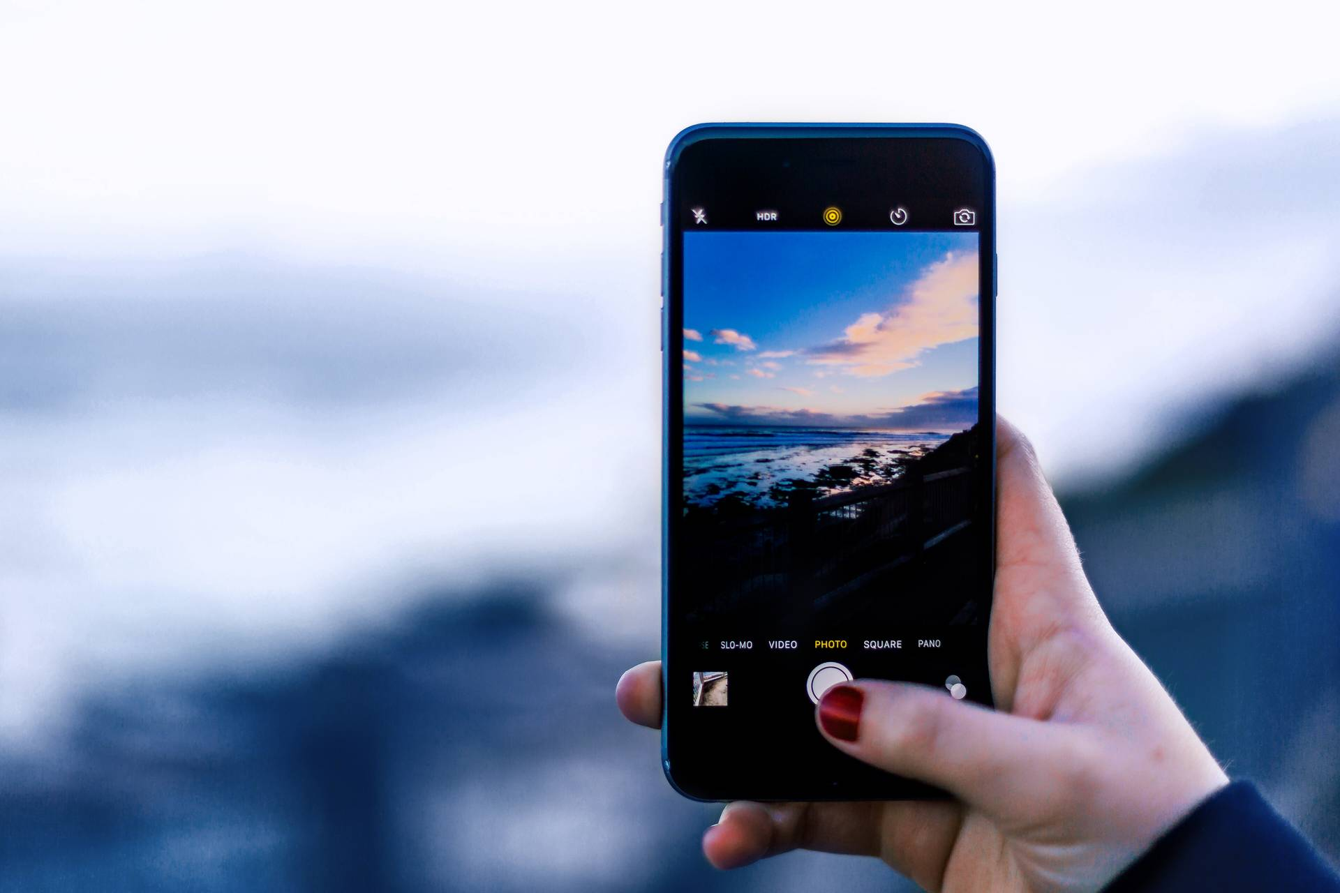 En kvinna fotograferar en strand med sin mobil