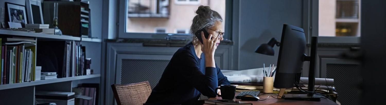 Kvinna vid skrivbord i hemmamiljö, pratar i telefon framför dator.