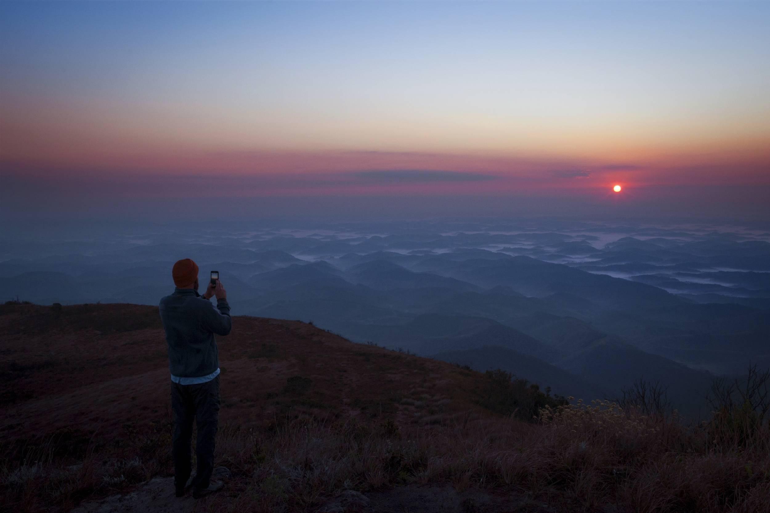 En man fotograferar solnedgången