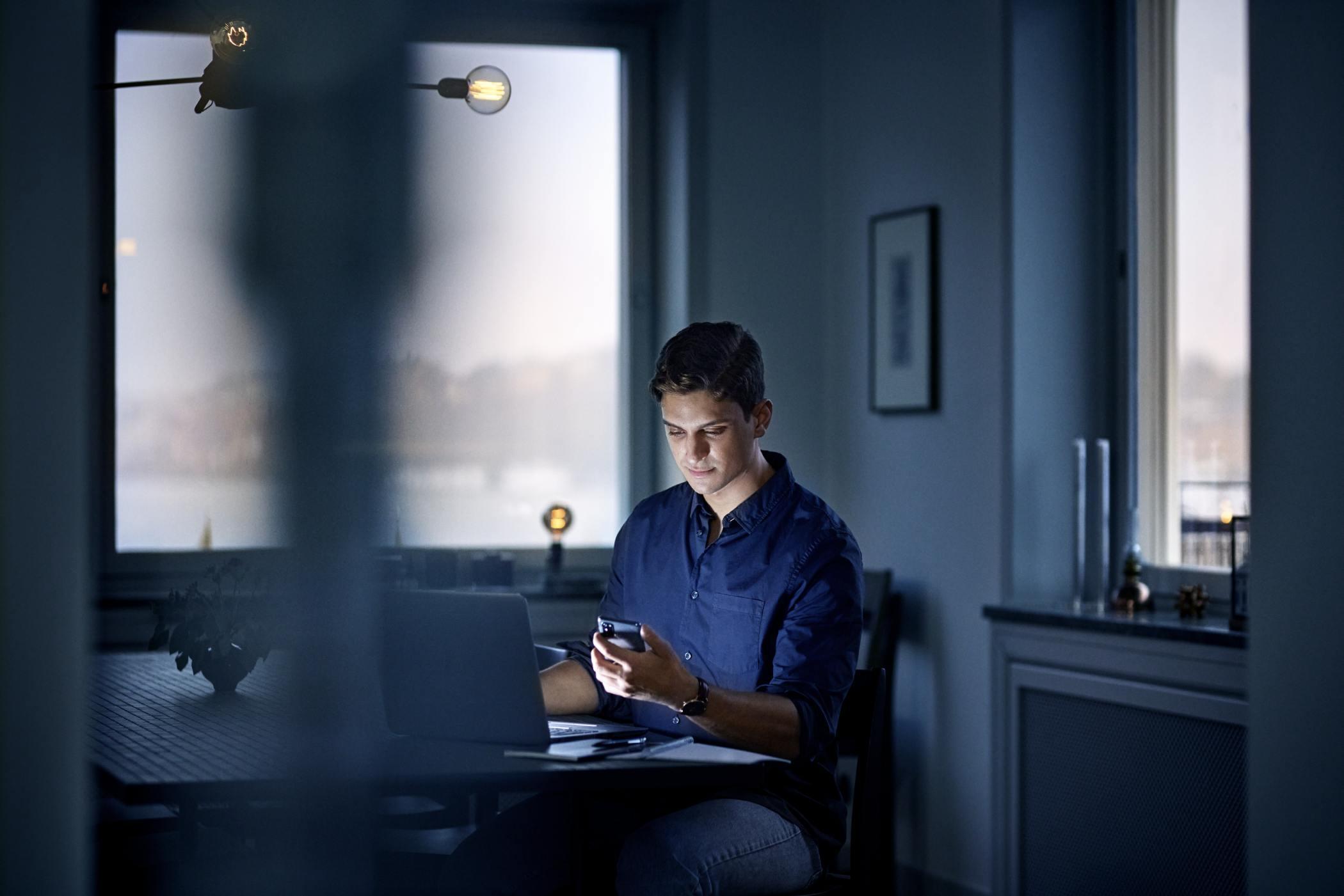 Ung man sitter med mobil och jobbar hemifrån.
