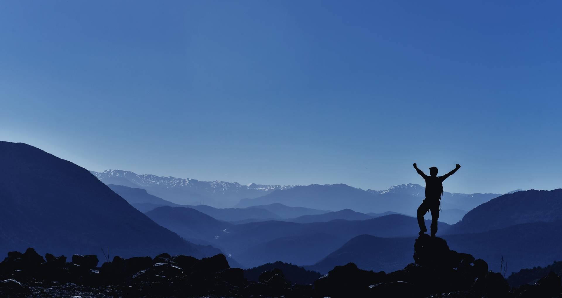 Man sträcker triumferande upp armarna efter att ha bestigit en bergstopp