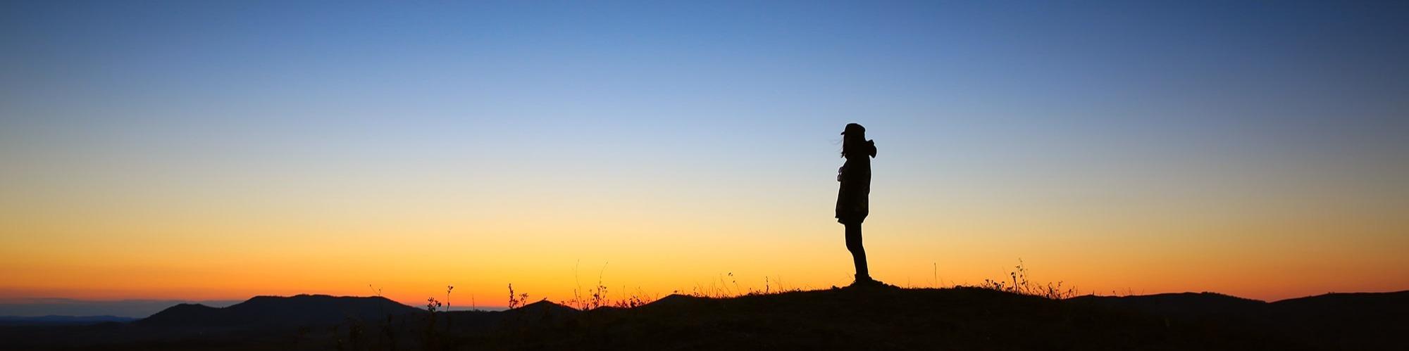 Solnedgång med person i motljus.