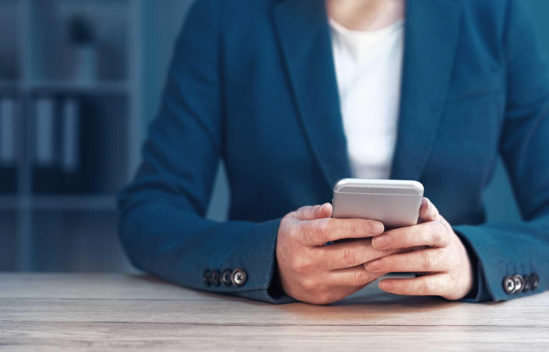 En kvinna i kavaj sitter med sin mobil