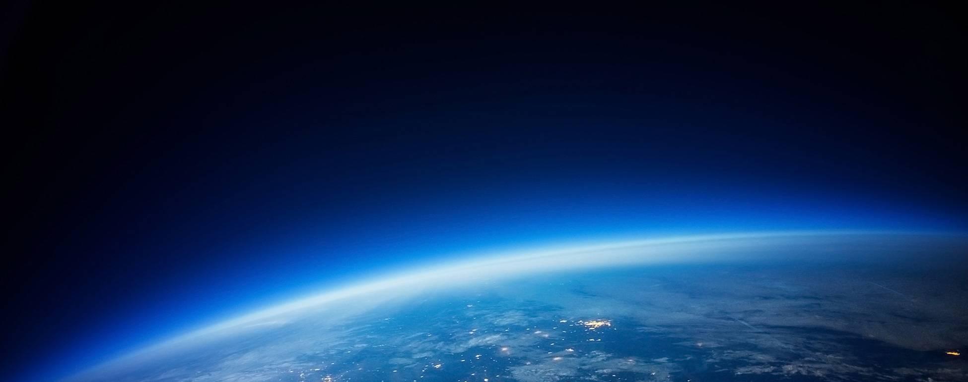 Jorden blåtonad svart himmel