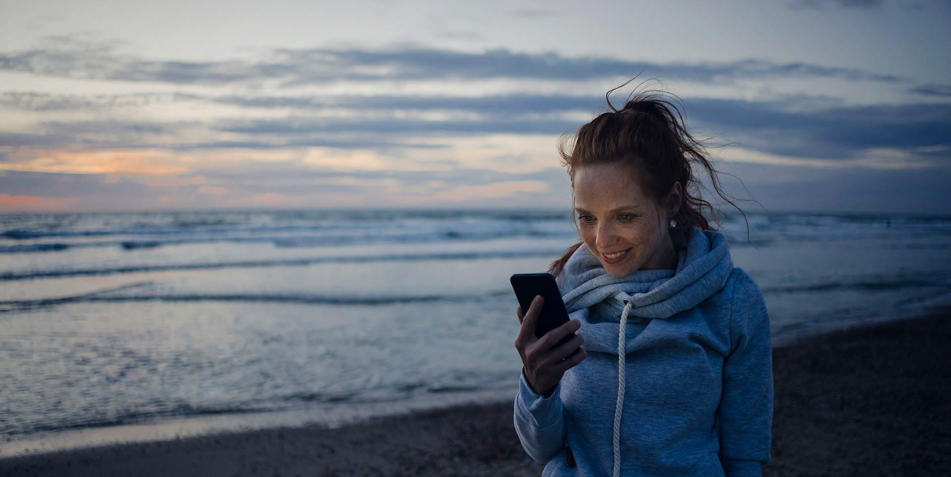 Leende kvinna står vid stranden och tittar på sin mobil. På Tele2 Företag erbjuder vi förmåner för företag som samlar sina tjänster hos oss.