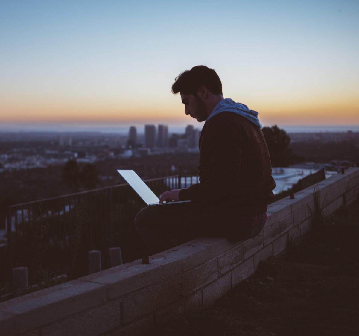 Men Tele2 Företag kan du vara obegränsat flexibel och ta med dig jobbdatorn överallt, som denna unge man som valt att ta med sig sin laptop för att kunna arbeta på en vacker utsiktsplats.