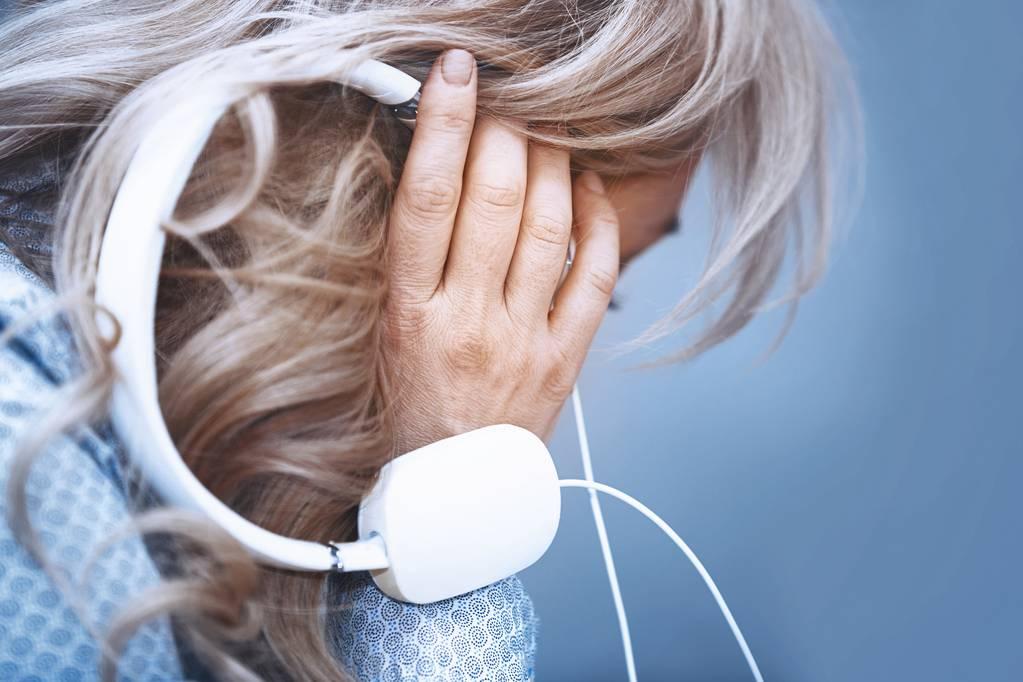 En kvinna håller i ett par hörlurar
