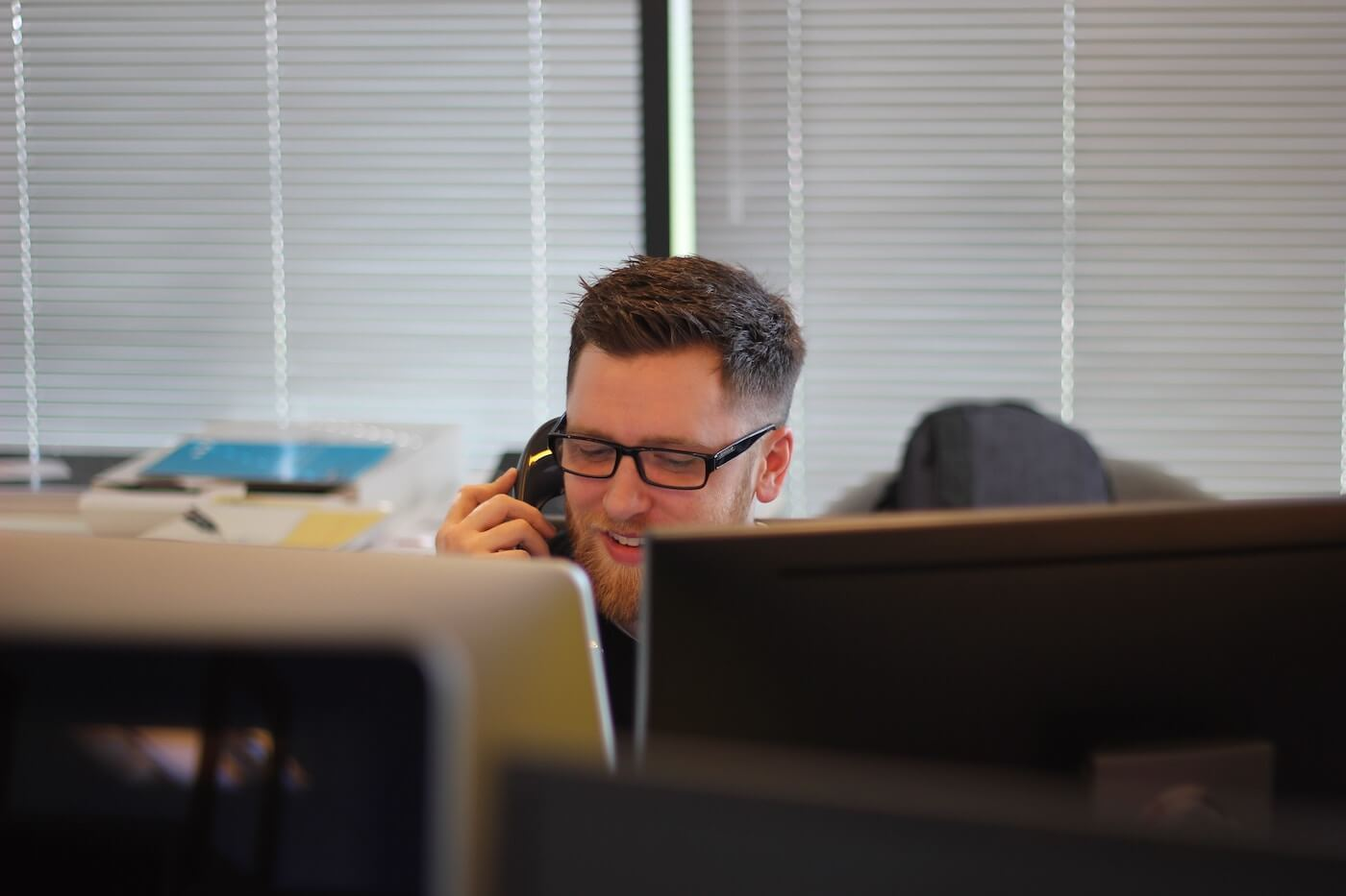 man sitting at a computer taking a phone call